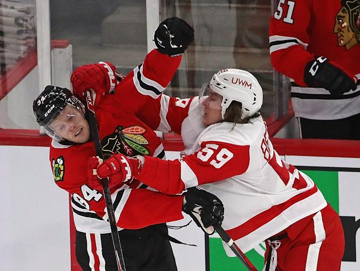 Carl Soderberg of the Chicago Blackhawks and Tyler Bertuzzi of the Detroit Red Wings get into a shoving match in front of the Blackhawks bench at the United Center on Jan. 24, 2021, in Chicago
