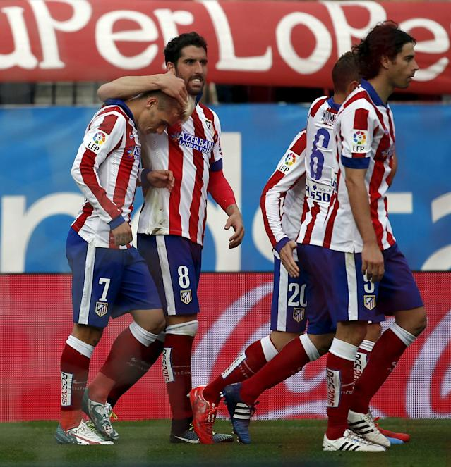 Atletico Madrid's Antoine Griezmann (L) is congratulated by teammate Raul Garcia after scoring against Elche during their Spanish first division soccer match at Vicente Calderon stadium in Madrid, April 25, 2015. REUTERS/Susana Vera