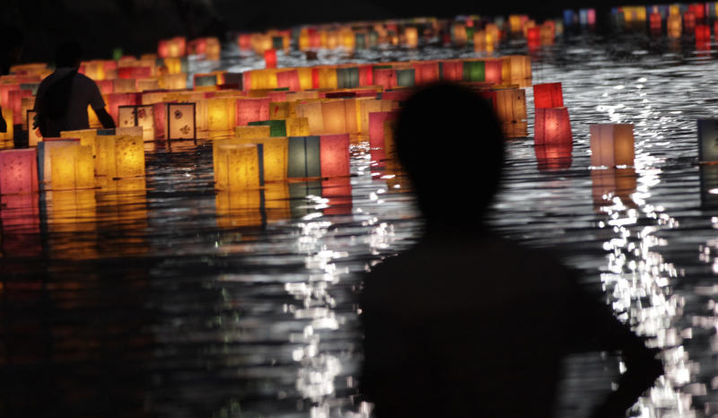 A man watches paper lanterns for the repose of the souls of the atomic bombing victims in the Motoyasu River near the Atomic Bomb Dome in Hiroshima, western Japan, Tuesday, Aug. 6, 2013. Japan marked the 68th anniversary Tuesday of the atomic bombing of Hiroshima with a somber ceremony to honor the dead and pledges to seek to eliminate nuclear weapons. (AP Photo/Shizuo Kambayashi)