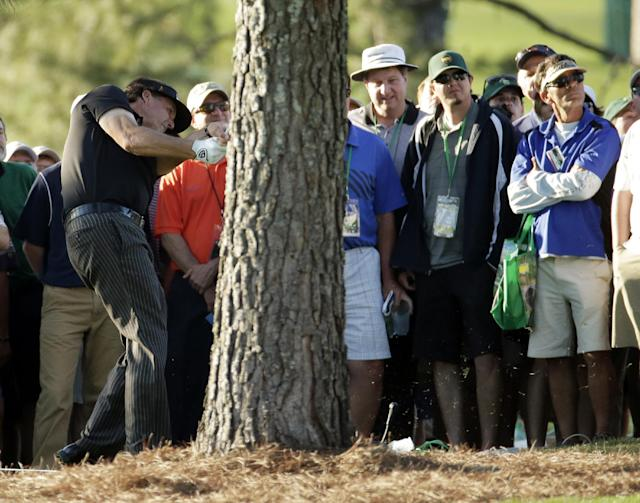 Phil Mickelson hits from behind a tree off the 17th hole during the first round of the Masters golf tournament Thursday, April 10, 2014, in Augusta, Ga. (AP Photo/Charlie Riedel)