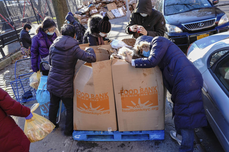 Photo by: John Nacion/STAR MAX/IPx 2020 12/26/20 People are seen rummaging through leftover Food Bank boxes in Flushing Borough of Queens, a day after Christmas Day on December 26, 2020.
