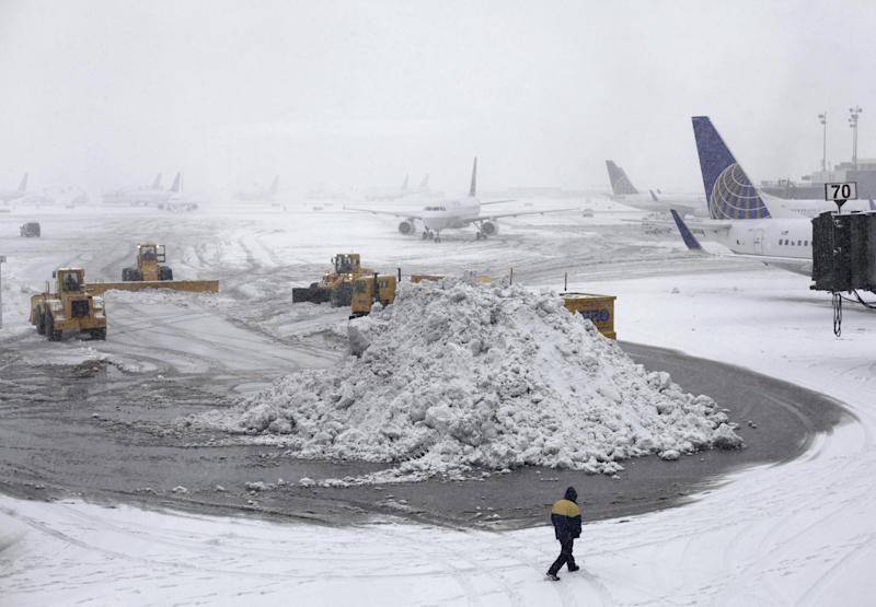 Plows clear runways as snow falls at Newark Liberty International Airport, Monday, Feb. 3, 2014, in Newark, N.J. Air traffic is disrupted in Ohio, the Mid-Atlantic and the Northeast as another winter storm bears down on the eastern U.S., only a day after temperatures soared into the 50s. (AP Photo/Kiichiro Sato)