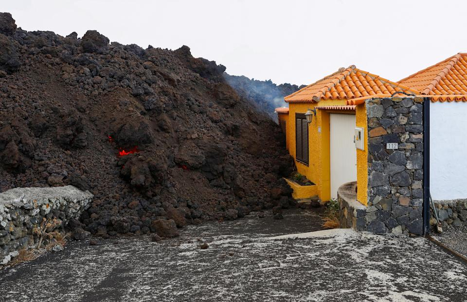 Lava reaches a house following the eruption of a volcano in the Cumbre Vieja national park, in the residential area of Los Campitos at Los Llanos de Aridane, on the Canary Island of La Palma, September 20, 2021. REUTERS/Borja Suarez