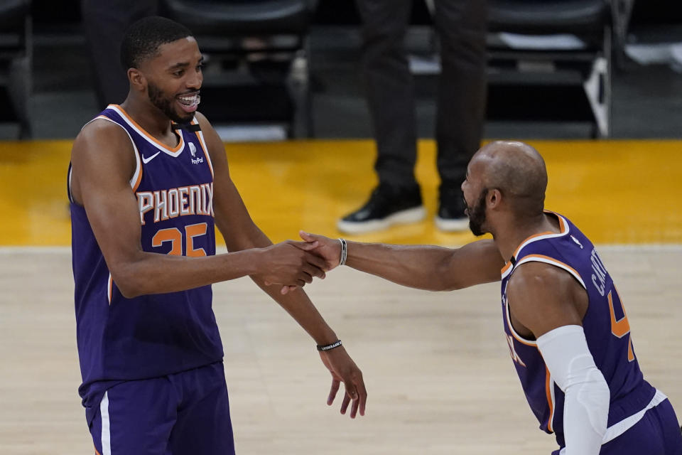 Phoenix Suns forward Mikal Bridges (25) and guard Jevon Carter (4) celebrate after winning 113-100 over the Los Angeles Lakers of Game 6 of an NBA basketball first-round playoff series Thursday, June 3, 2021, in Los Angeles. The Suns won the series 4-2 and will move on to round 2. (AP Photo/Ashley Landis)