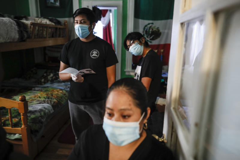 Family members wear personal protective equipment as the Rev. Fabian Arias performs an in-home service beside the remains of Raul Luis Lopez who died from COVID-19 the previous month, Saturday, May 9, 2020, in the Corona neighborhood of the Queens borough of New York. (AP Photo/John Minchillo)
