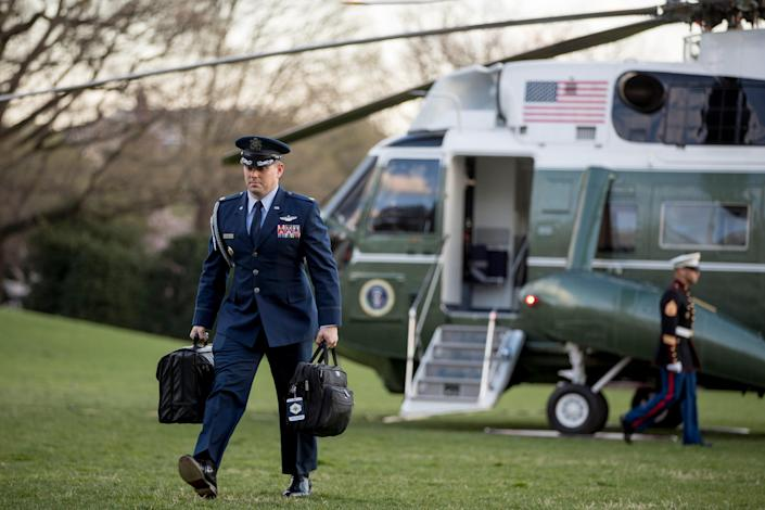 "A US military aide carries the ""president's emergency satchel."""