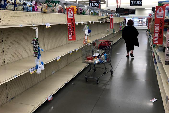 A woman shops among empty shelves at a Hy-Vee food store on March 13, in Overland Park, Kansas.