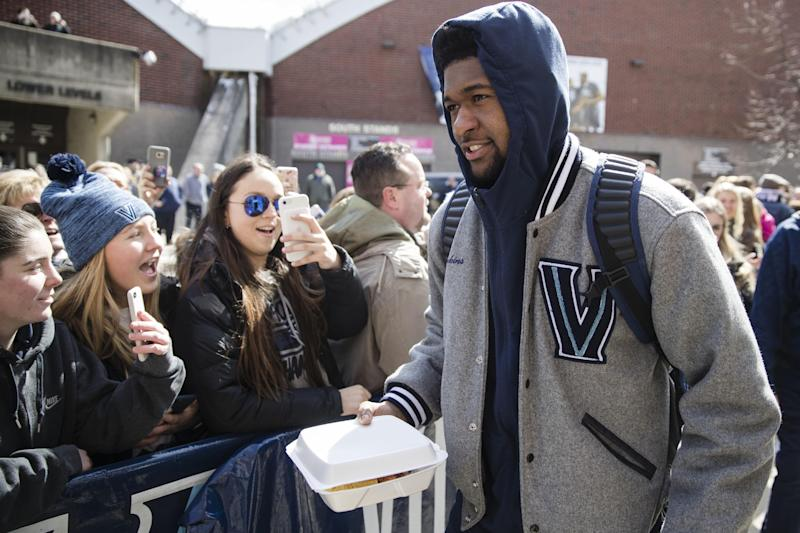 Villanova NCAA college basketball player Kris Jenkins talks to fans before boarding a bus as the team departs Villanova, Pa., on Monday, March 13, 2017, for a game in the first round of the NCAA Tournament, in Buffalo, N.Y. Teams chasing a college basketball title are contending with an unexpected wrinkle that's making last-minute travel plans even tougher: the anticipation of a storm bearing down on the Northeast that's expected to dump snow and wind. (AP Photo/Matt Rourke)nam