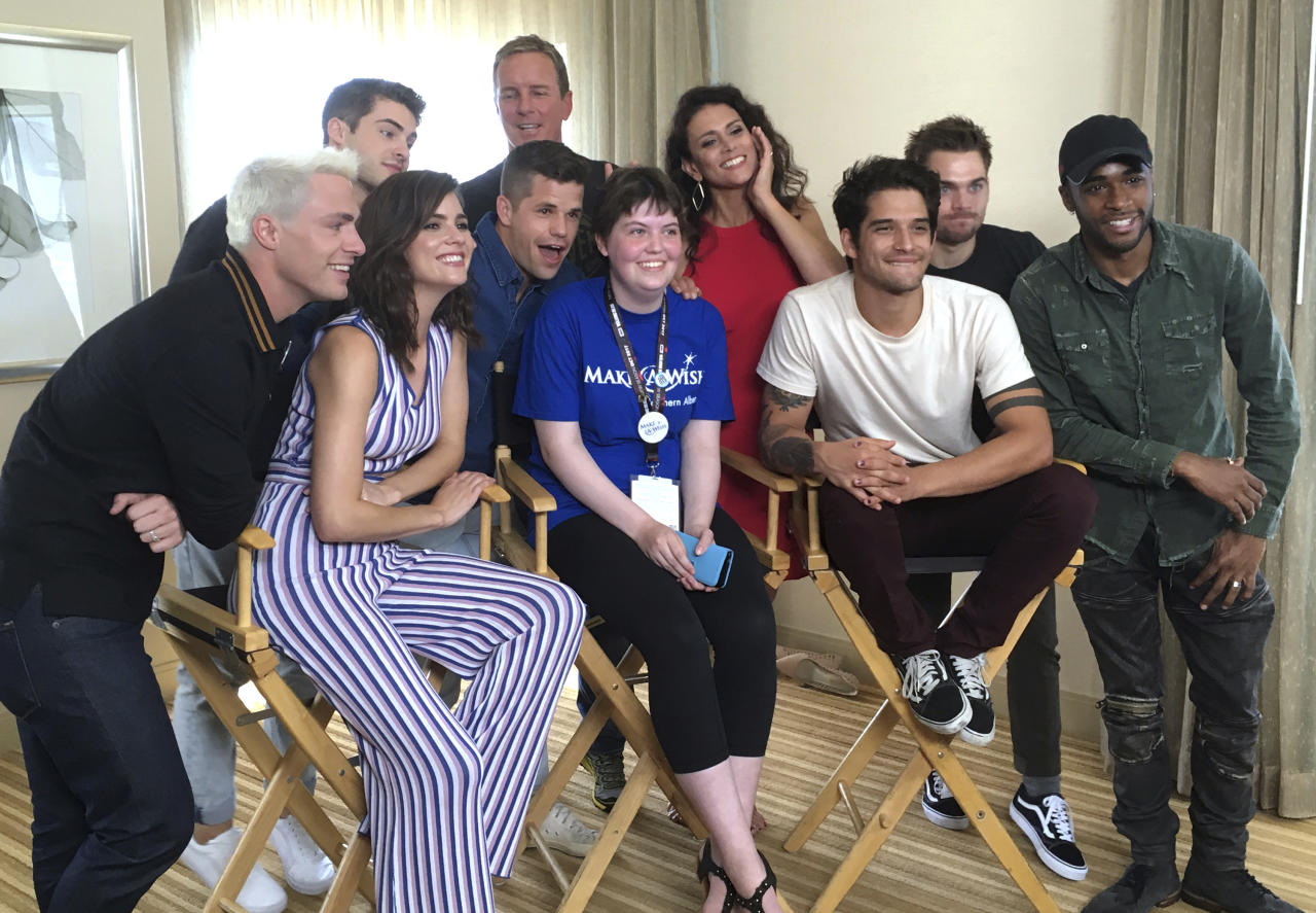 "Sydney Lang, 16, of Edmonton, Alberta, seated center, poses with cast members from ""Teen Wolf"" during a meet-and-greet arranged by the Make-A-Wish Foundation on day two of Comic-Con International on Friday, July 21, 2017, in San Diego. Pictured from front row left, Colton Haynes, Shelley Hennig, Charlie Carver, Tyler Posey and Khylin Rhambo, and from back row left are Cody Christian, Linden Ashby, Melissa Ponzio, and Dylan Sprayberry. (AP Photo/Sandy Cohen)"