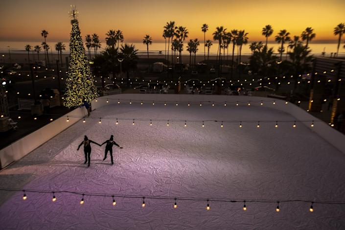Two people ice skate on an outdoor rink. In the background is a lighted Christmas tree, palm trees and the ocean.