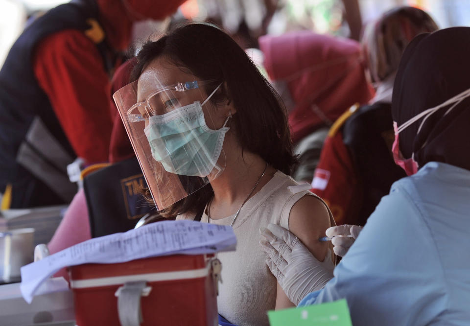 A woman receives a shot of the Sinovac COVID-19 vaccine at a soccer stadium in Bandung, West Java, Indonesia, Thursday, June 17, 2021. Indonesia's president ordered authorities to speed up the country's vaccination campaign as the World Health Organization warned Thursday of the need to increase social restrictions in the country amid a fresh surge of coronavirus infections caused by worrisome variants. (AP Photo/Bukbis Candra)