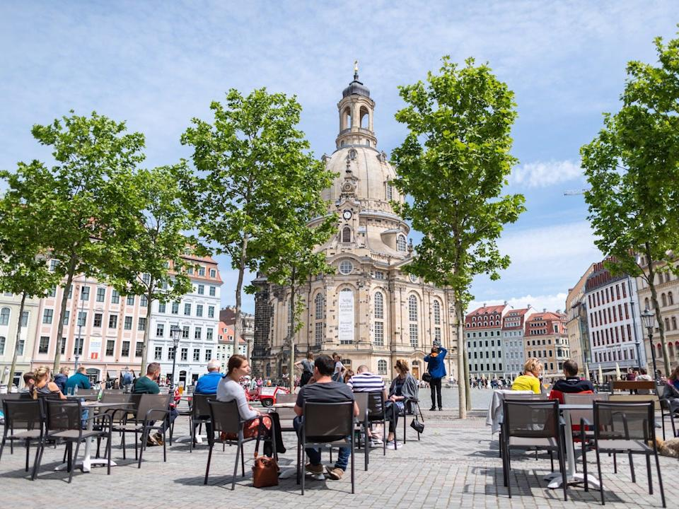 Guests sit at tables of restaurants on the Neumarkt in front of the Frauenkirche in Dresden on May 22, 2020.