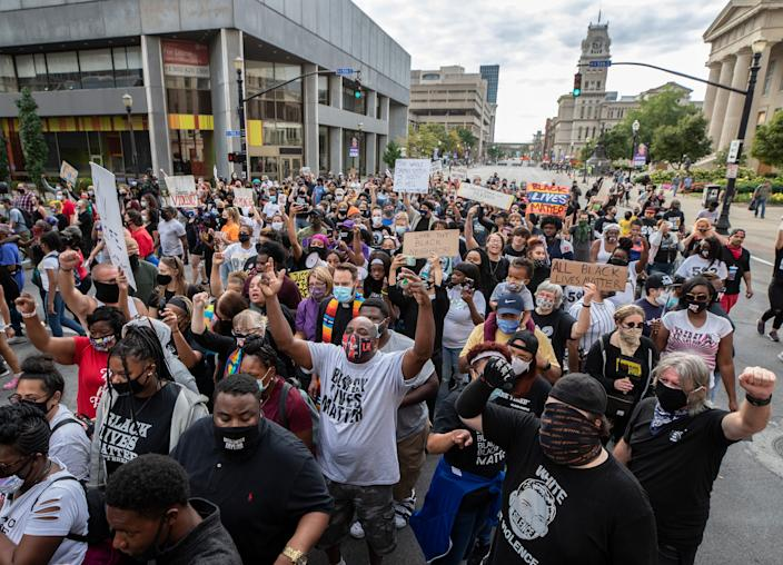 Protesters squeeze between Alice barricade as they march from Jefferson Square to the NuLu district in Louisville. Sept. 25, 2020.
