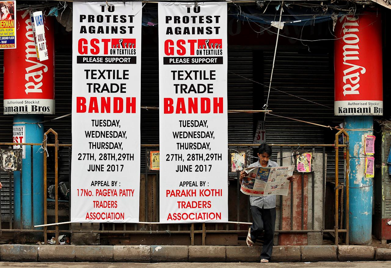 A man reads a newspaper next to banners in front of a closed garments market, during a protest against the implementation of the Goods and Services Tax (GST) on textiles, in Kolkata, India June 29, 2017. REUTERS/Rupak De Chowdhuri