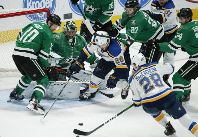 St. Louis Blues forward Mackenzie MacEachern (28) and St. Louis Blues forward Nathan Walker (26) battle Dallas Stars for the puck during the second period of an NHL hockey game Friday, Nov. 29, 2019, in Dallas. (AP Photo/Brandon Wade)