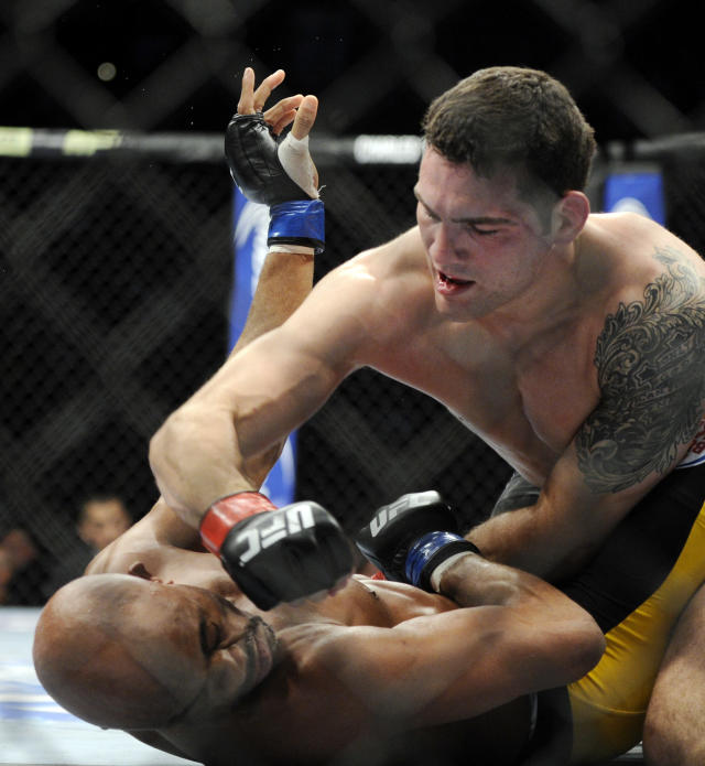 Chris Weidman, top, of Baldwin, N.Y., punches Anderson Silva of Brazil during the UFC 168 mixed martial arts middleweight championship bout at the MGM Grand Garden Arena, Saturday, Dec. 28, 2013, in Las Vegas. Weidman won by a technical knockout during the second round after Silva was injured. (AP Photo/David Becker)