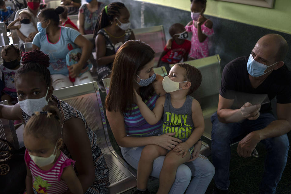 Parents wait to have their children vaccinated with the Soberana-02 COVID-19 vaccine, at a clinic in Havana, Cuba, Thursday, Sept. 16, 2021. Cuba began inoculating children as young as 2-years-old with locally developed vaccines on Thursday. (AP Photo/Ramon Espinosa)