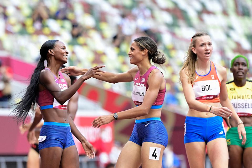 Sydney Mclaughlin reacts after winning the women's 400m hurdles final with Dalilah Muhammad as Femke Bol looks on (AFP)