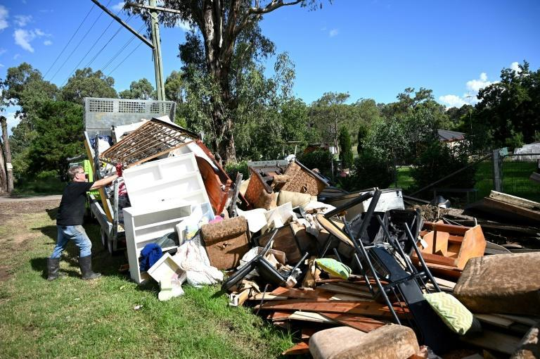 A man piles up damaged possessions outside his house in Londonderry, a suburb outside Sydney, as flood-stricken residents along Australia's east coast began a massive clean up effort following days of floods