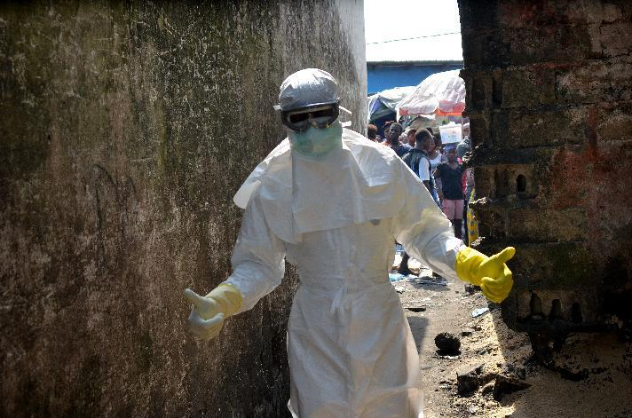 A Red Cross worker prepares to bury Ebola victims in Monrovia, on January 5, 2015 (AFP Photo/Zoom Dosso)