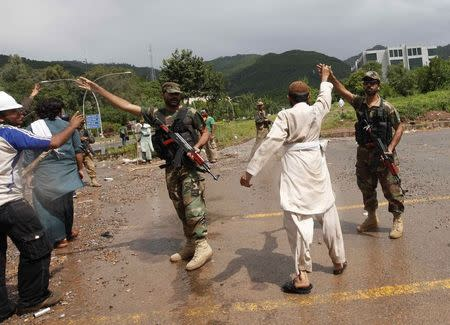 A supporter (2nd R) of Tahir ul-Qadri, Sufi cleric and leader of political party Pakistan Awami Tehreek (PAT), lifts up the hand of a Pakistan Army soldier, during the Revolution March towards the prime minister's house in Islamabad September 1, 2014. REUTERS/Akhtar Soomro