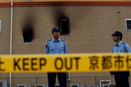 Policemen stand behind a police line at the torched Kyoto Animation building in Kyoto