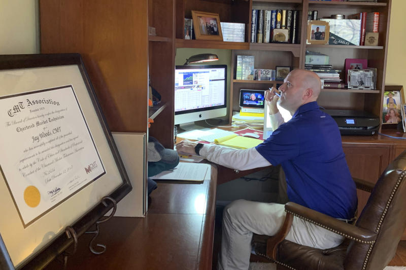 In this image provided by Jay Woods,  Woods, a Designated Market Maker with IMC and NYSE Floor Governor, who normally works on the New York Stock Exchange trading floor, works in his home office in Basking Ridge, N.J., Thursday, March 26, 2020.  Stocks are opening lower on Wall Street as the market gives back some of the gains it piled up over the past three days. (Shannon Woods/Courtesy Jay Woods via AP)