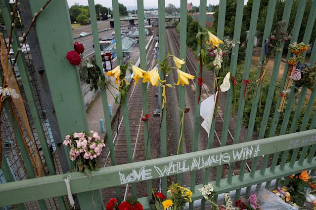 <p>Flowers hang on a makeshift memorial for two men who were killed on a commuter train while trying to stop another man from harassing two young women who appeared to be Muslim, in Portland, Ore., May 29, 2017. (Terray Sylvester/Reuters) </p>