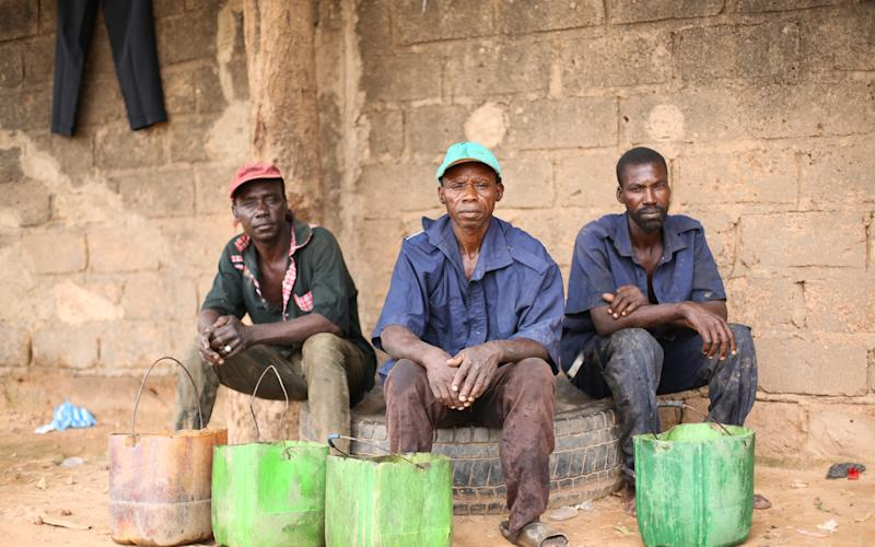 Three workers in Burkina Faso take a break after emptying a latrine - Basile Ouedraogo/Water Aid