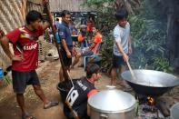 Men prepare food during a death anniversary in the Kayan village where people, who fled from Myanmar during the 1990s war between Myanmar's army and ethnic army groups, live in Mae Hong Son