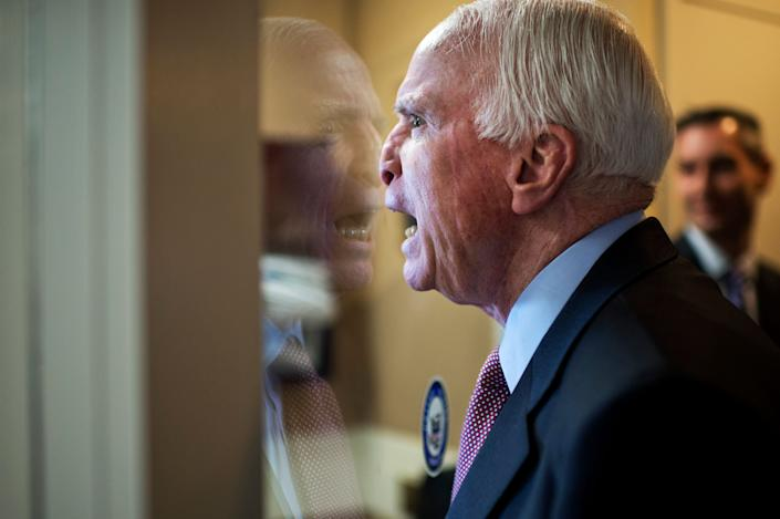 Sen. John McCain (R-Ariz.) fools around with colleagues upon arriving for a news conference on Guantanamo detainees in the Senate studio on Jan. 13, 2015.