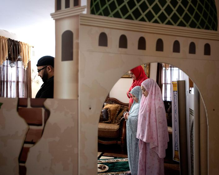 From left, Eyad Asmar, his wife, Ramia, and daughters Touleen, 8, and Noor, 11, pray at their homemade mosque on May 8.