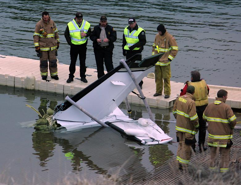 This photo provided by the Ouray County Plaindealer shows rescue personnel examining the tail second of a plane on Saturday, March 22, 2014 after it was recovered from the Ridgeway Reservoir south of Montrose. Colo. The plane believed to be carrying five people crashed into a reservoir in southwestern Colorado and authorities say all are feared dead. Divers are to be used Sunday to search for victims and to recover the rest of the plane. (AP Photo/Ouray County Plaindealer, Patrick Moore) MANDATORY CREDIT