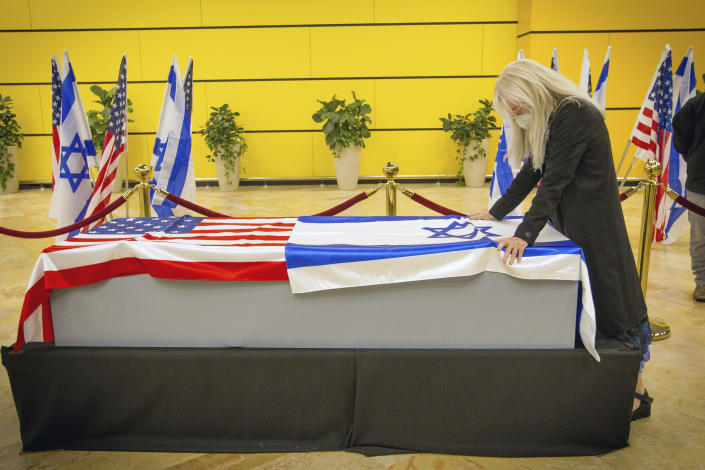 Miriam Adelson touches the casket of her husband, Sheldon Adelson upon arrival to Ben Gurion Airport, near the city of Lod, Israel, Thursday, Jan. 14, 2021. Adelson, the billionaire mogul and power broker who built a casino empire spanning from Las Vegas to China and became a singular force in domestic and international politics has died after a long illness, his wife said Tuesday, Jan. 12, 2021. (Ami Shooman, Israel Hayom/ Pool Photo via AP)