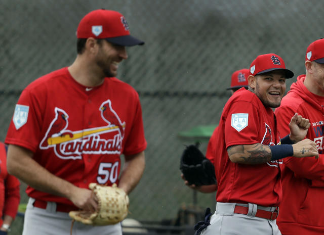 St. Louis Cardinals catcher Yadier Molina, right, laughs after receiving a kiss on the cheek from teammate Adam Wainwright, left, as Wainwright walked past during spring training baseball practice Wednesday, Feb. 13, 2019, in Jupiter, Fla. (AP Photo/Jeff Roberson)