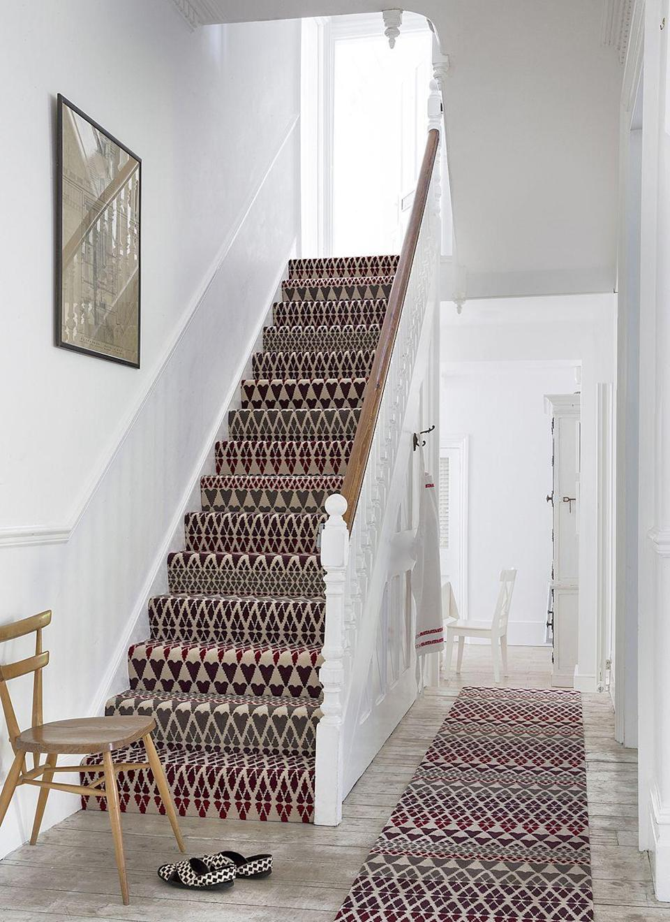 """<p>Pristine white walls and light wooden floors are the perfect base for brave design choices. Here, Margo Selby's signature geometric pattern in a colourful mixture of burgundy, cream and green becomes a real feature - doubly so by matching a stair carpet with a runner. </p><p>Pictured: <a href=""""https://www.alternativeflooring.com/collection/quirky_b/quirky_b__margo_selby_collection/quirky_b_fair_isle/annie.html"""" rel=""""nofollow noopener"""" target=""""_blank"""" data-ylk=""""slk:Margo Selby Fair Isle Annie Carpet at Alternative Flooring"""" class=""""link rapid-noclick-resp"""">Margo Selby Fair Isle Annie Carpet at Alternative Flooring</a></p>"""
