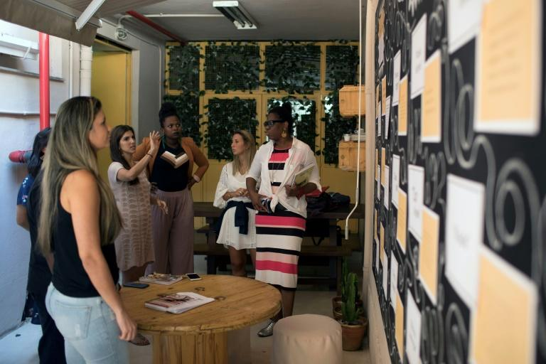 Employees of fashion brand Maria Filo talk about a mural developed with the support of the anti-racism group ID_BR in Rio de Janeiro, Brazil, on November 17, 2017
