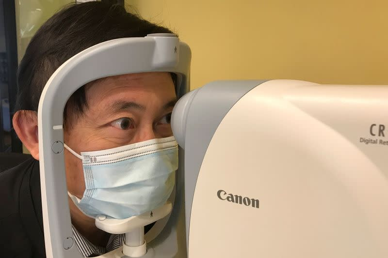 Benny Zee demonstrates retinal eye scanning technology used for early detection of autism in Hong Kong