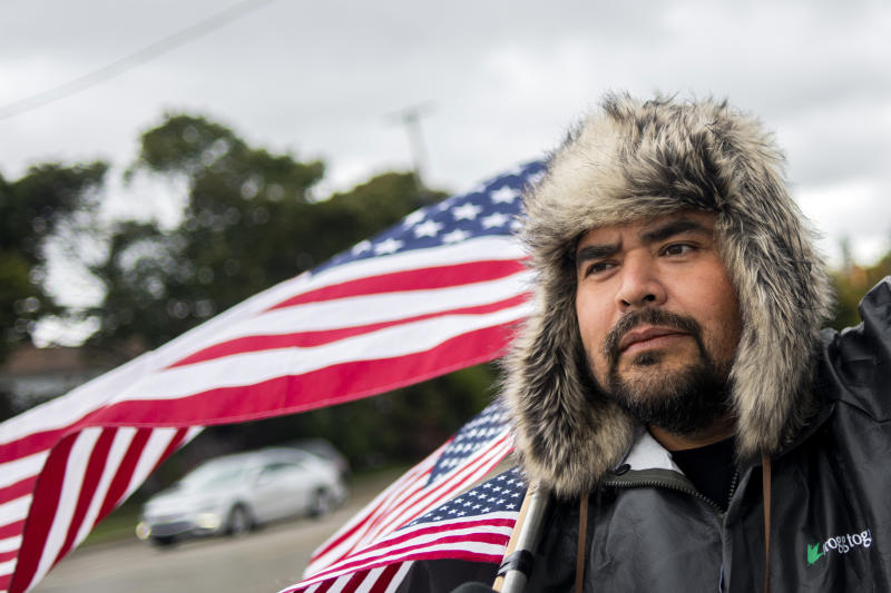 "Michael Perez, 48 of Saginaw, stand with waving American flags to show solidarity alongside other General Motors' Flint Assembly Plant employees and UAW members, who line the street with picket signs on the 31st day of the nationwide UAW strike against GM after stalled contract negotiations on Wednesday, Oct. 16, 2019, outside of the Flint Assembly Plant in Flint, Mich. Perez has been employed as an electrician in the body shop for more than 10 years. ÒWe get to keep our job and our health insurance, but we're mainly fighting for the younger crowd and the future of this plant,"" Perez said. (Jake May/The Flint Journal via AP)"
