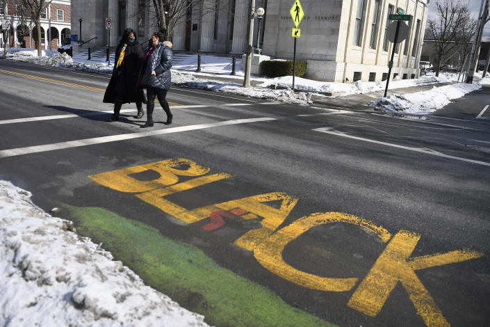 In this Saturday, Feb. 20, 2021, photo, Mia Schultz, president of the Rutland area branch of the NAACP, right, walks with town Select Board candidate Tina Cook past a Black Lives Matter mural on a street in Bennington, Vt. A number of protesters, including some who carried an anti-Black Lives Matter sign, stood in the way during painting of the mural, forcing those working on the mural to paint around their feet and bodies blocking the letters. Cook came up short in the March 2 election in her effort to become the first African American elected to the board. (AP Photo/Jessica Hill)