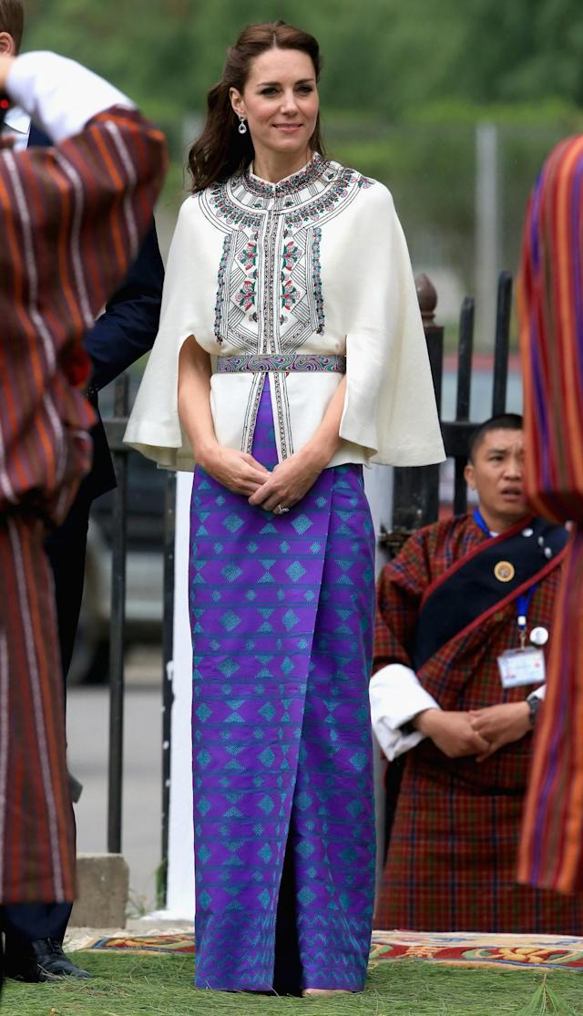 <p>For a game of archery, the Duchess paired a traditional Bhutanese skirt with an embroidered Paul and Joe cape. <br><em>[Photo: PA] </em> </p>