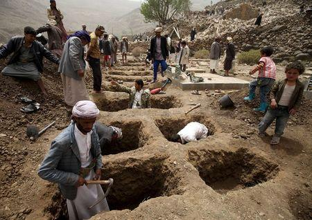 People dig graves for the victims of an air strike in Okash village near Sanaa