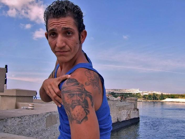 Cuban cigar maker Yoan Avila shows his newly done tattoo depicting President Fidel Castro in Havana on January 30, 2007 (AFP Photo/Adalberto Rooque)