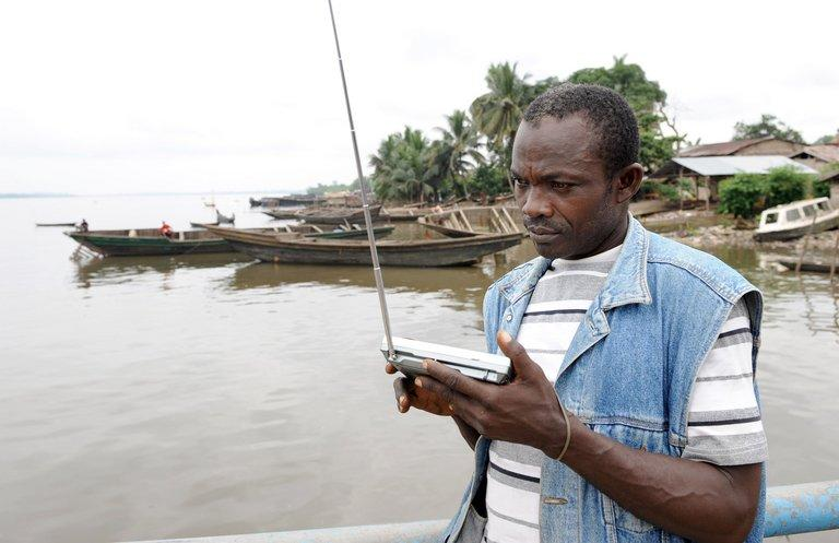A a man listens to the radio on August 14, 2008 at Ikang River, in Cross River State, Nigeria