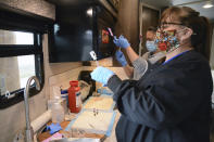 In this Thursday, April 29, 2021, photo, Roberta Wagner, foreground, a health clinic administrator for the Blackfeet tribe, prepares COVID-19 vaccine doses to be administered to Canadian residents at the Piegan-Carway border crossing near Babb, Mont. The Blackfeet tribe gave out surplus vaccines in April to its First Nations relatives and others from across the border. (AP Photo/Iris Samuels)