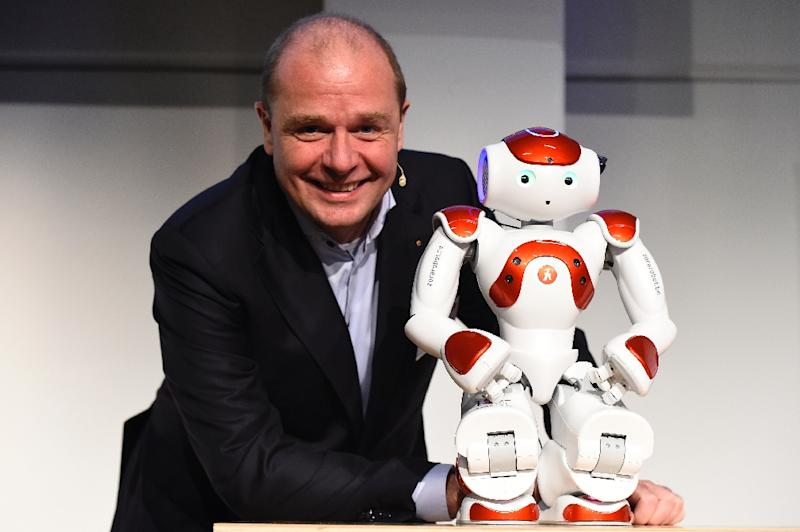 Co-Chief Executive Officer of QBMT/Zora Robotics Fabrice Goffin poses next to robot Mario who is multi-lingual, greets guests, helps with serving at hotel buffets, and entertains by singing and dancing (AFP Photo/Tobias Schwarz                      )