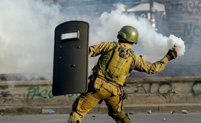 A riot police aims a tear gas canister at demonstrators during clashes which erupted during a protest against the government of Chilean President Sebastian Pinera in Santiago on January 24, 2020