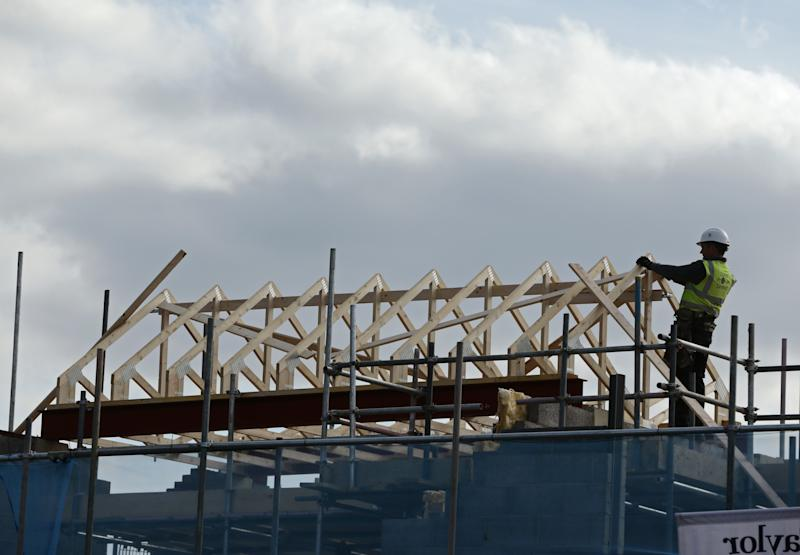 Construction workers building the roof of a new house under construction at Taylor Wimpey�s Churchill Place development in Mill Hill, London. PRESS ASSOCIATION Photo. Picture date: Friday March 27, 2015. Photo credit should read: Yui Mok/PA Wire