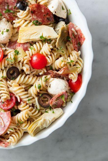 """<p>Olives, tomatoes, salami and mozzarella balls. What more could you want?</p><p>Get the <a href=""""https://www.delish.com/uk/cooking/recipes/a30526942/easy-pasta-salad-recipe/"""" rel=""""nofollow noopener"""" target=""""_blank"""" data-ylk=""""slk:Italian Pasta Salad"""" class=""""link rapid-noclick-resp"""">Italian Pasta Salad</a> recipe.</p>"""