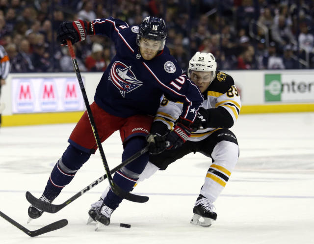 Columbus Blue Jackets forward Alexander Wennberg, left, of Sweden, works against Boston Bruins forward Karson Kuhlman during the second period of an NHL hockey game in Columbus, Ohio, Tuesday, April 2, 2019. (AP Photo/Paul Vernon)